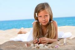 Muchacha dulce que juega con los shelles en la playa. imagenes de archivo