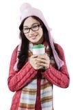 Muchacha dulce que lleva la bebida caliente caliente de la ropa y de los controles Fotos de archivo