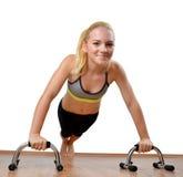 Muchacha durante los músculos pectorales del ejercicio en el fondo blanco Imágenes de archivo libres de regalías