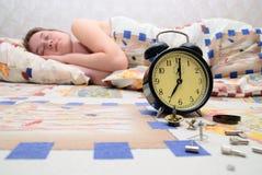 Muchacha durmiente cercana del reloj de alarma quebrado Imagen de archivo libre de regalías