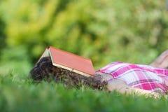 Muchacha durmiente con el libro en la cabeza Imagen de archivo libre de regalías