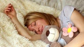 Muchacha durmiente con el oso de peluche en dormitorio en casa almacen de video