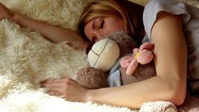Muchacha durmiente con el oso de peluche en dormitorio en casa metrajes