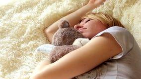 Muchacha durmiente con el oso de peluche en dormitorio en casa almacen de metraje de vídeo