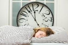 muchacha durmiente en cama con el despertador, Fotos de archivo libres de regalías