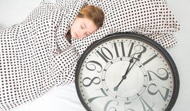 muchacha durmiente en cama con el despertador, Fotografía de archivo libre de regalías