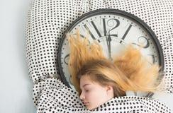 muchacha durmiente en cama con el despertador, Imagenes de archivo