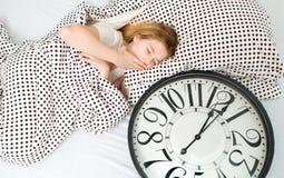 muchacha durmiente en cama con el despertador, Fotografía de archivo