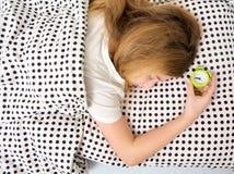 muchacha durmiente en cama con el despertador, Imágenes de archivo libres de regalías