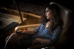 Muchacha durmiente en una silla con el telecontrol de la TV Fotografía de archivo libre de regalías