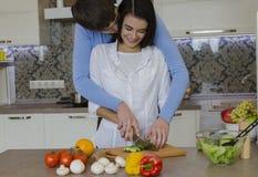Muchacha e individuo en la cocina que prepara la comida fotos de archivo