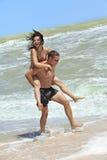 Muchacha e individuo en la playa Fotografía de archivo