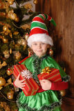 Muchacha - el duende de la Navidad con un regalo Imagen de archivo