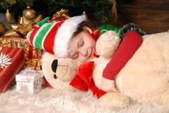 Muchacha - el duende de la Navidad duerme bajo un abeto Fotografía de archivo libre de regalías