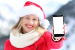 Muchacha el los días de fiesta de la Navidad que muestran la pantalla del teléfono Foto de archivo