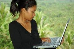 Muchacha el vacaciones usando el ordenador portátil afuera fotografía de archivo libre de regalías