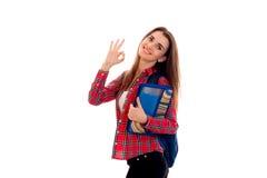 Muchacha elegante alegre del estudiante con la mochila en sus hombros y carpeta para los cuadernos en sus manos que presentan y q Imagenes de archivo
