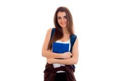 Muchacha elegante alegre del estudiante con la mochila en sus hombros y libros en sus manos que sonríe en la cámara aislada en bl Imagenes de archivo