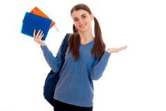Muchacha elegante alegre del estudiante con las coletas y la mochila en sus hombros que sonríe en cámara con los libros en sus ma Fotografía de archivo