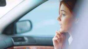 Muchacha elegante asombrosa con el pelo rojo en chaqueta marrón clara y la camiseta blanca que habla por el smartphone que se sie almacen de video