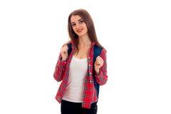 Muchacha elegante bastante elegante del estudiante con la mochila en sus hombros que presentan y que sonríen en la cámara aislada Imagen de archivo libre de regalías