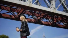 Muchacha elegante con café en el fondo del puente almacen de metraje de vídeo