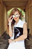 Muchacha elegante con el bolso en gafas de sol Fotos de archivo