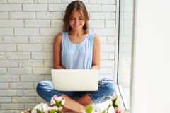 Muchacha elegante con el ordenador portátil que se sienta en ventana-travesaño con la pierna de las cruces Fotografía de archivo