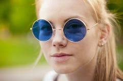 Muchacha elegante con las gafas de sol retras redondas púrpuras Fotos de archivo libres de regalías