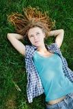 Muchacha elegante con los dreadlocks que mienten en hierba verde Foto de archivo libre de regalías