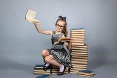 Muchacha elegante con una pila de libros Foto de archivo libre de regalías