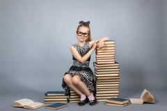 Muchacha elegante con una pila de libros Imagen de archivo libre de regalías