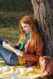 Muchacha elegante concentrada que lee un libro debajo del árbol Fotos de archivo