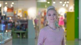 Muchacha elegante de la belleza con los panieres que presentan en el centro comercial después de hacer compras