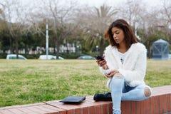 Muchacha elegante del inconformista que sostiene el teléfono elegante mientras que se sienta en el parque al aire libre Fotografía de archivo libre de regalías