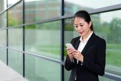 Muchacha elegante del oficinista que usa el teléfono celular móvil Imágenes de archivo libres de regalías