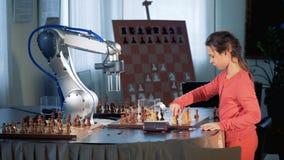Muchacha elegante del scgool que juega al ajedrez con un brazo robótico, robot del ajedrez Concepto del genio del niño almacen de metraje de vídeo