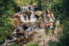 Muchacha elegante del viajero que sostiene la hoja del helecho en la cascada en las FO soleadas Imagenes de archivo