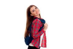 Muchacha elegante elegante alegre del estudiante con la mochila en sus hombros que presentan y que sonríen en la cámara aislada e Fotografía de archivo