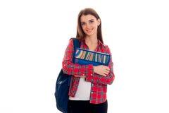 Muchacha elegante elegante alegre del estudiante con la mochila en sus hombros y carpetas para los cuadernos en las manos que pre Fotos de archivo libres de regalías