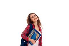 Muchacha elegante elegante feliz del estudiante con la mochila en sus hombros y carpetas para los cuadernos en las manos que pres Fotografía de archivo