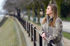 Muchacha elegante en abrigo de pieles que camina solamente en callejón de la ciudad del invierno Imagenes de archivo