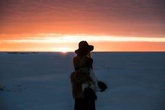 Muchacha elegante en abrigo de pieles y sombrero en la puesta del sol Foto de archivo