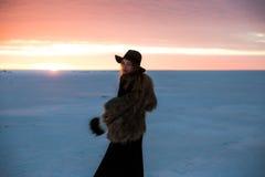 Muchacha elegante en abrigo de pieles y sombrero en la puesta del sol Imagenes de archivo