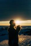 Muchacha elegante en abrigo de pieles y sombrero en la puesta del sol Imagen de archivo