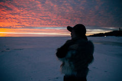 Muchacha elegante en abrigo de pieles y sombrero en la puesta del sol Imágenes de archivo libres de regalías