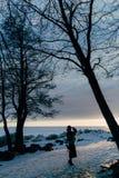 Muchacha elegante en abrigo de pieles y sombrero en la puesta del sol Fotografía de archivo