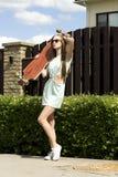 Muchacha elegante en actitudes de las gafas de sol con longboard fotos de archivo