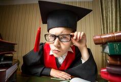 Muchacha elegante en el casquillo y las lentes de la graduación que miran la cámara Imágenes de archivo libres de regalías