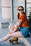 muchacha elegante en el patín de ruedas y las gafas de sol que se sientan en la escalera y la mirada foto de archivo